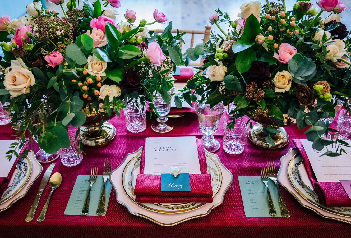 Spring wedding tablecentres with compote bowls and burgundy styling.